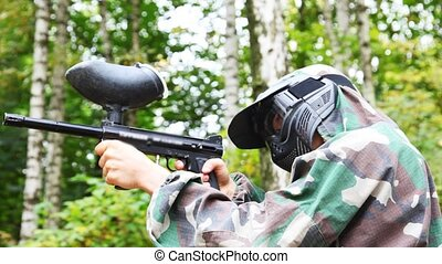 man in helmet and mask with paintball gun stand and pretends that aims