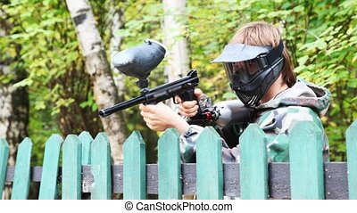 man in helmet and mask with paintball gun stands up for fence and pretends that shoots
