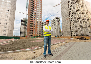 Man in helmet and safety vest standing on building site