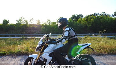 Man in helmet driving powerful sport motorbike along highway. Motorcyclist riding on motorcycle through country road. Young guy enjoying speed at sunny day. Freedom concept. Slow motion Side view