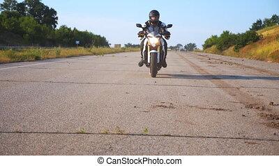 Man in helmet driving powerful sport motorbike at highway. ...