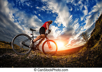 Man in helmet on the bicycle against cloudy sky
