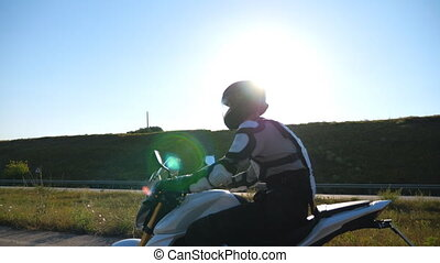 Man in helmet riding fast on modern sport motorbike at highway. Motorcyclist speeding his motorcycle through country road. Guy in moto equipment driving bike during trip. Adventure or freedom concept