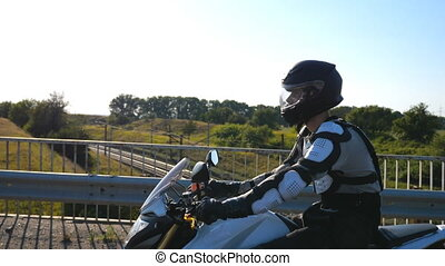 Man in helmet riding fast on powerful sport motorbike at highway. Motorcyclist racing his motorcycle on country road. Guy in moto equipment driving bike during trip. Concept of adventure and freedom