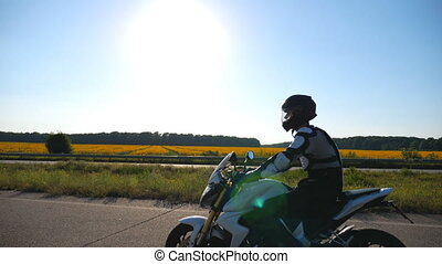 Man in helmet riding fast on powerful sport motorbike at highway. Motorcyclist racing his motorcycle against scenic nature view. Guy in protective equipment enjoying trip. Adventure or freedom concept