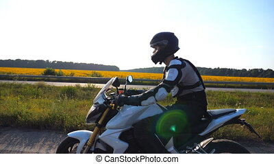 Man in helmet riding fast on sport motorbike along highway with scenic view at background. Motorcyclist speeding on motorcycle through country road. Guy enjoying speed. Freedom concept. Side view