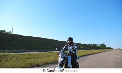 Man in helmet riding fast on sport motorbike at highway. Motorcyclist racing his motorcycle against scenic nature view. Guy in protective equipment enjoying trip. Adventure or freedom concept. Slow mo
