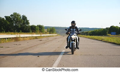 Man in helmet riding on fast sport motorbike at highway. Motorcyclist racing his motorcycle against scenic nature view. Guy in protective equipment enjoying trip. Adventure or freedom concept. Slow mo