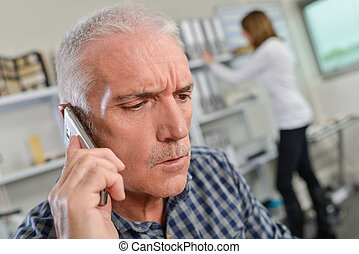 Man in his office on the phone