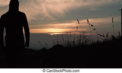 Man in hood goes near the field in the dark evening. Slow motion