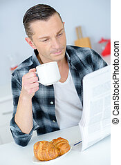 man in hotel room reading newspaper with breakfast in bed