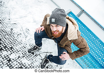 Man in ice skates sitting on the bench outdoors