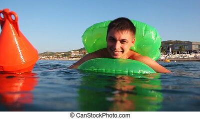 Man in inflatable disc is afraid, can not swim, clings buoy into sea