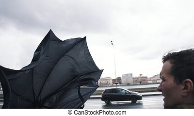 Man in jacket with umbrella. The gust of wind pulls umbrella out of hand of man