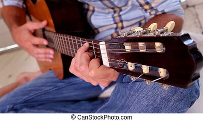 Man in jeans and check shirt playing guitar at home in the...
