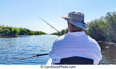 Man in kayak fishing with artificial lure