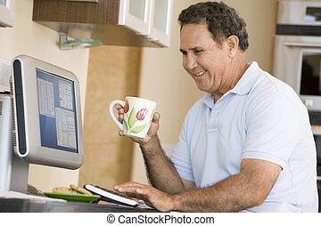 man, in, keuken, met, computer, en, koffie, het glimlachen