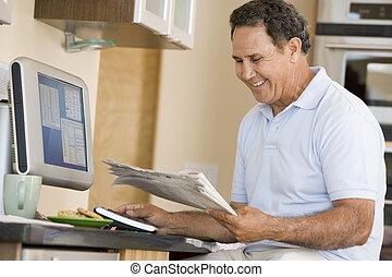man, in, keuken, met, computer, en, krant, het glimlachen