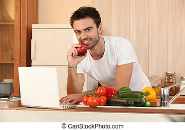 Man in kitchen with laptop and vegetables