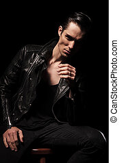man in leather jacket posing seated while resting