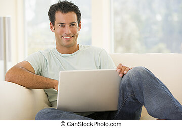 Man in living room using laptop smiling