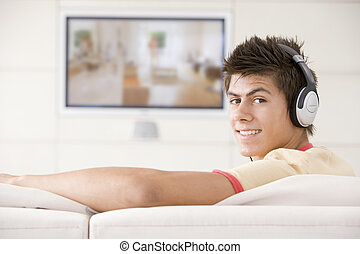 Man in living room watching television and wearing...