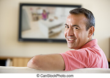 Man in living room watching television smiling