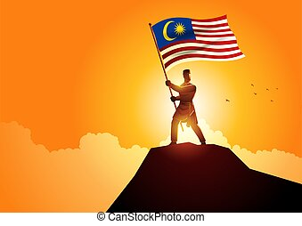 Man in malay traditional costume holding the flag of Malaysia on mountain peak