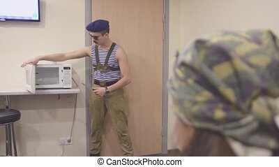 Man in marine shirt and cap, sunglasses open microwave with...