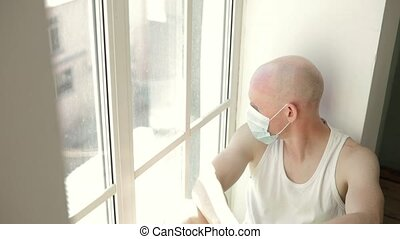Man in mask boring sitting on windowsill and looking at ...