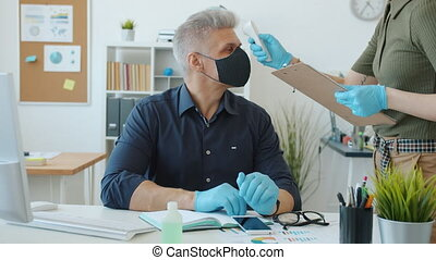 Man in mask is busy with computer work while female employee is taking his temperature with infrared thermometer concerned with safety in workplace.
