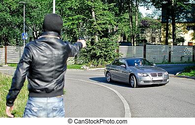 Man in mask pointing gun toward car. Robbery concept