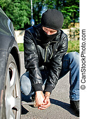 Man in mask punctures a car tyre. Revenge concept