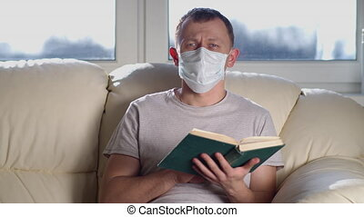 Man in medical mask with a book in his hands looks at the camera while sitting on a sofa