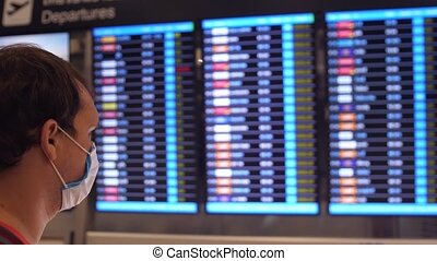 Man in medical masks from coronavirus look at the departure Board at an airport during global pandemic where all flights canceled. Covid-19.