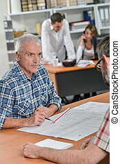 Man in meeting discussing blueprints