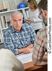 Man in meeting with couple, bemused facial expression