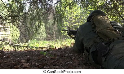 Man in military uniform with a weapon hides under tree.