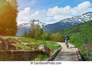 man in mountain landscape with bike