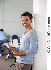 Man in office leaning against wall holding clipboard and pen
