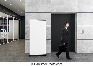 Man in office with elevator and poster