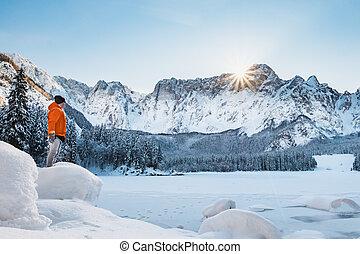 Man in orange jacket on frozen lake looking to mountain -...