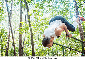 Man in outdoor gym doing exercise on the parallel bars