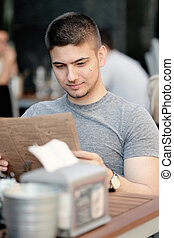 Man in outdoor restaurant looking at the menu