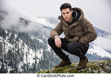 Man in outerwear sitting while looking at camera - Handsome ...
