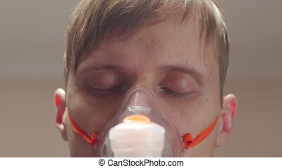 Man in oxygen mask napping looking at camera portrait eyes closeup interior