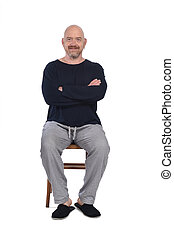 man in pajamas sitting o a chair on white background, arms crossed