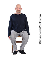 man in pajamas sitting o a chair on white background,