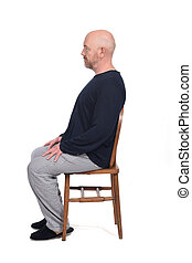 man in pajamas sitting o a chair on white background, side view