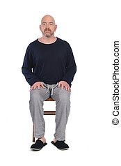 man in pajamas sitting o a chair on white background